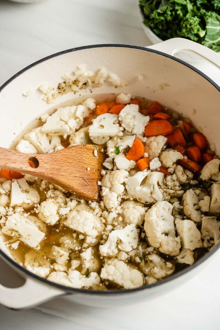Chopped cauliflower and carrot cooking in a large soup pot with a wooden spoon.