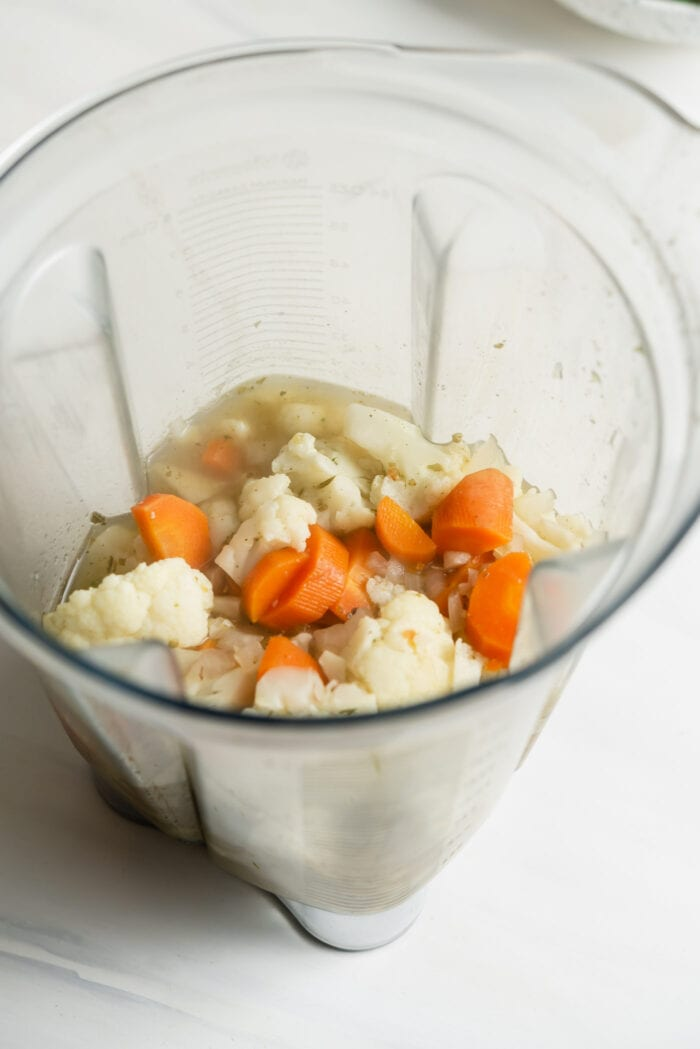 Carrots, vegetables and broth in a blender.