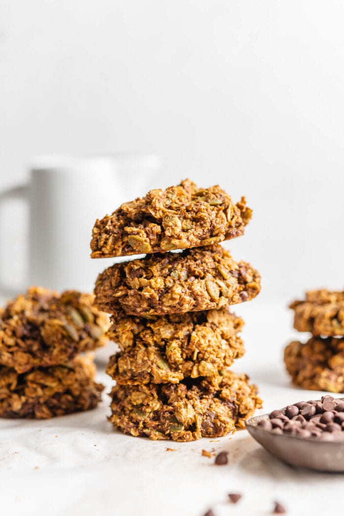 Stack of 4 cookies with a small dish of chocolate chips in foreground and more cookies in background.