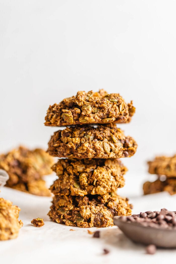 Stack of 4 hearty cookies with a small dish of chocolate chips in foreground and more cookies in background.