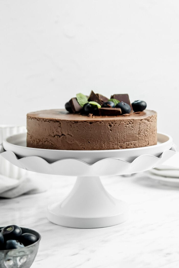 A chocolate cake topped with a few blueberries on a decorative cake stand.
