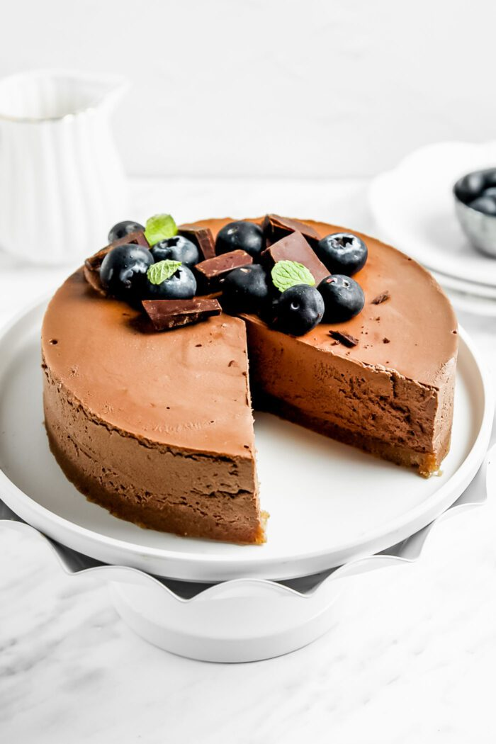 Raw chocolate cake with a slice taken from it on a decorative cake stand.