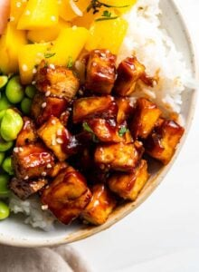 Close up of sweet and spicy tofu in a bowl with rice, mango and edamame.