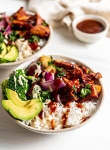 Two dinner bowls with rice, bbq tofu, avocado, broccoli, pineapple and roasted red onion.