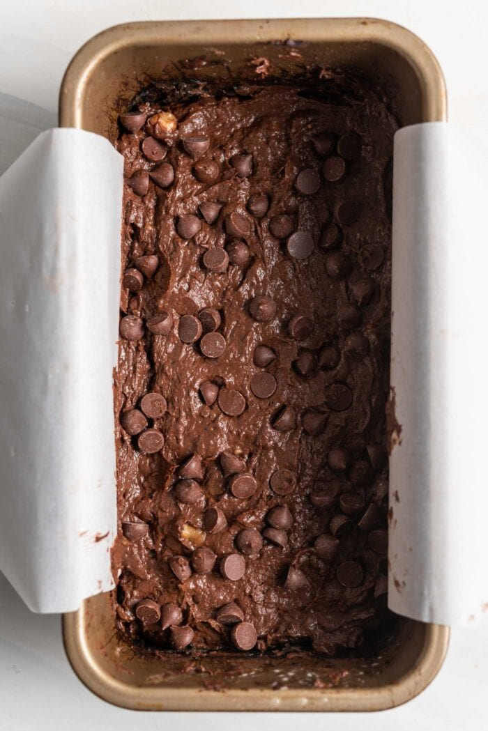 Raw chocolate chip brownie batter in a loaf pan.