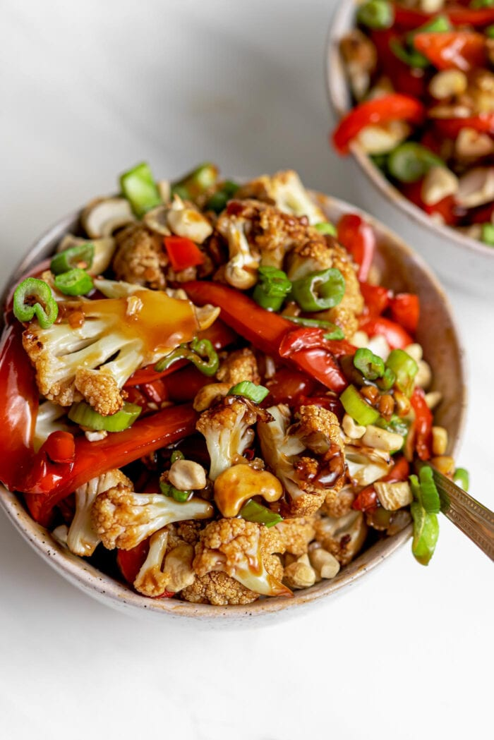 Two bowls of cauliflower kung pao topped with chopped green onions and cashews.