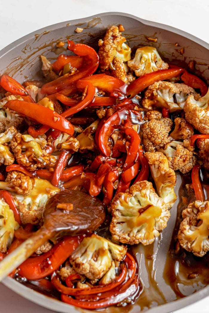 Cauliflower and bell peppers mixed in a thick brown sauce in a pan.