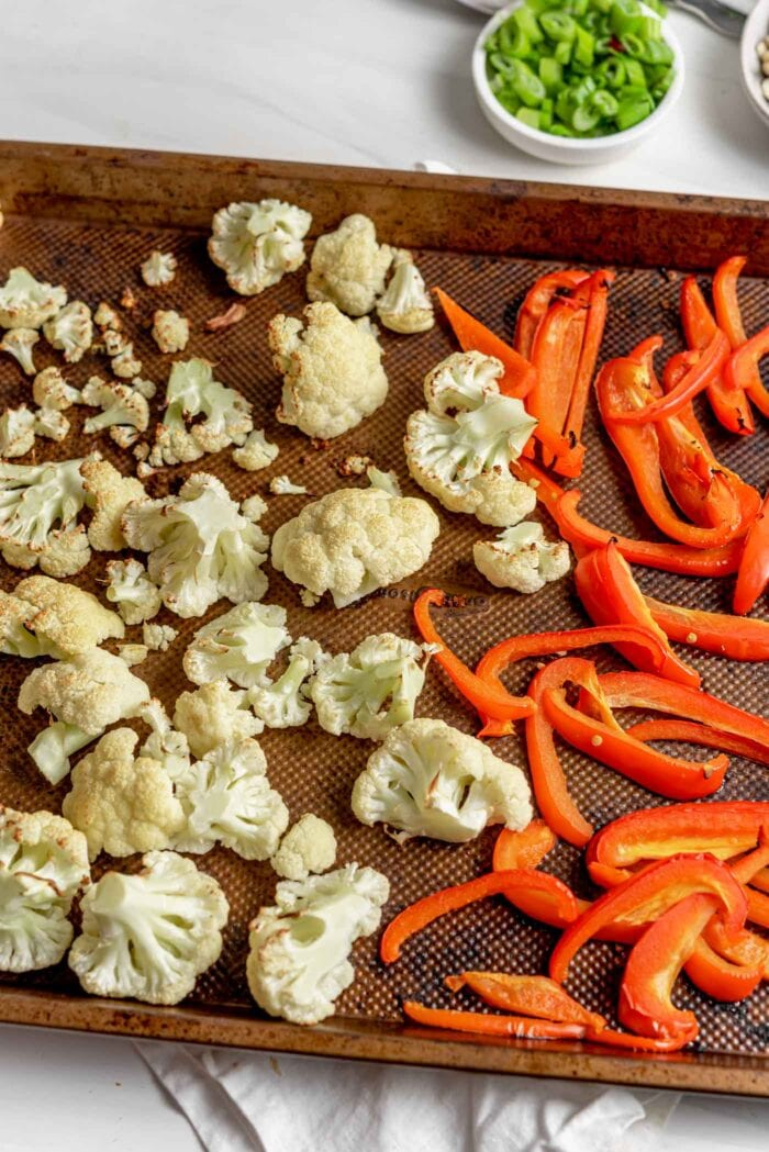 Roasted cauliflower and red bell peppers on a baking pan.