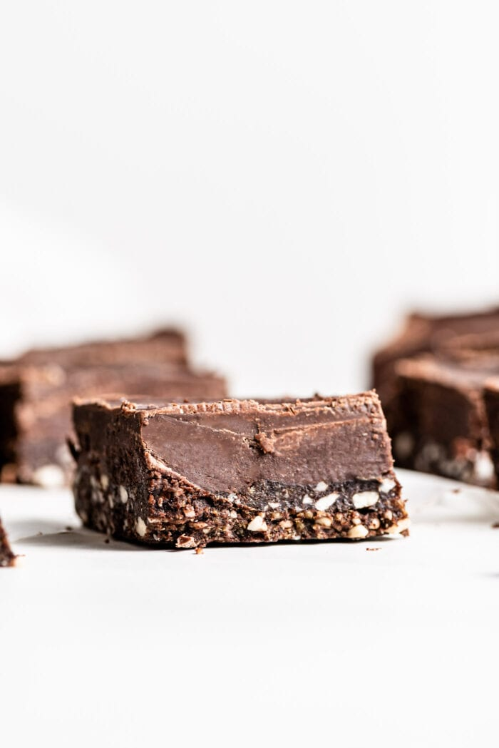 One triple layer chocolate square with a fudge-like texture in focus with a few more bars in the background.