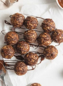 Overhead view of a number of no-bake energy balls drizzled in chocolate on a piece of parchment paper.
