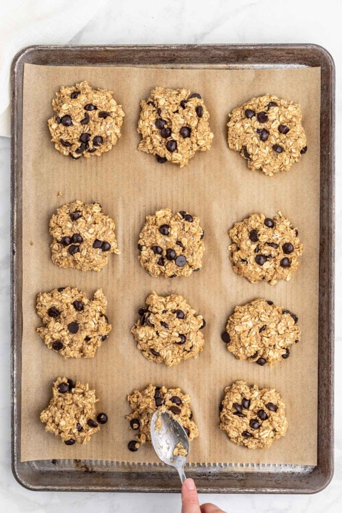 12 raw oatmeal chocolate chip cookies on a parchment paper-lined baking tray.