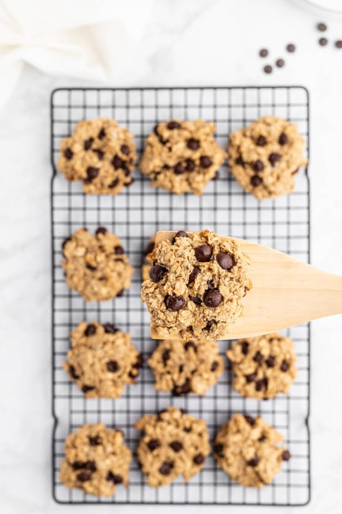 Wooden spatula with a cookie resting on it over a dozen cookies on a cooling rack.