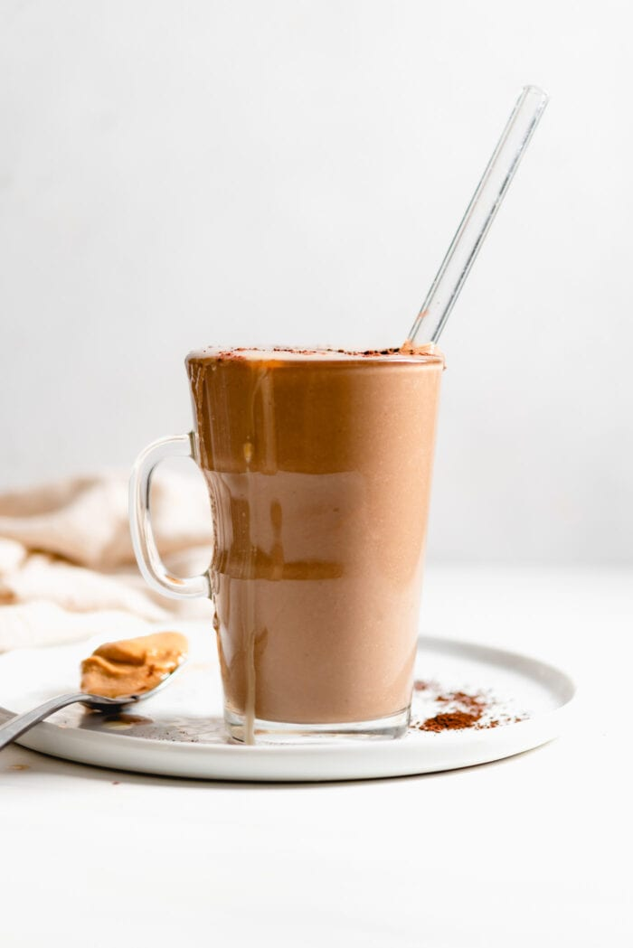 Creamy chocolate smoothie in a mug with a glass straw.
