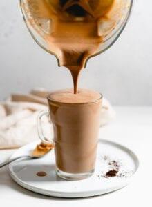 Blender pouring a chocolate smoothie into a glass mug.