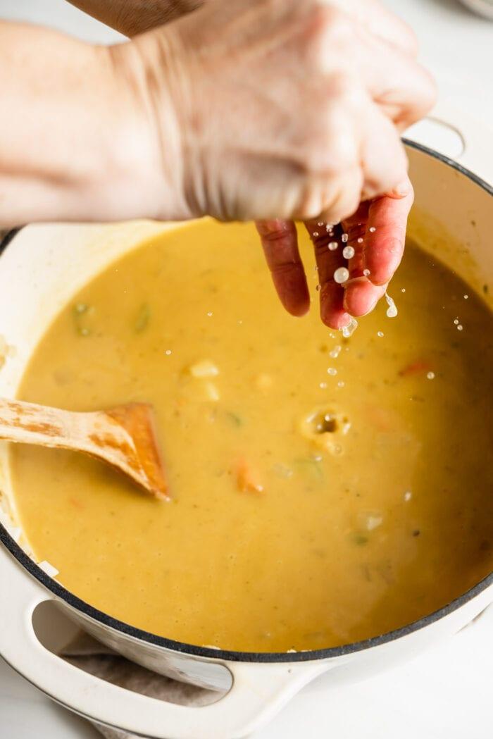 Squeezing fresh lemon juice into a pot of soup.