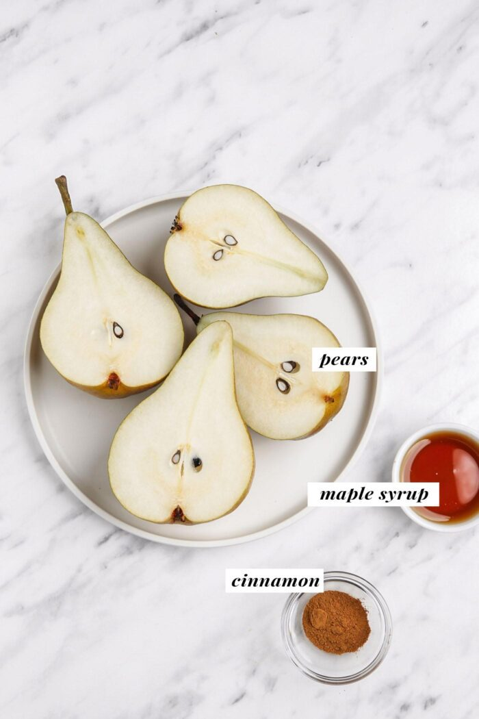 Sliced open pears on a small plate with small dishes of maple syrup and cinnamon beside them.