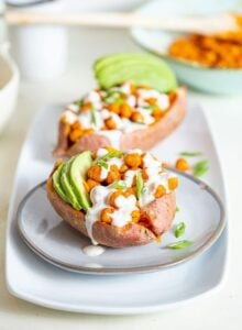 Sweet potato stuffed with buffalo chickpeas and avoado, topped with white sauce..