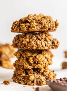 Stack of 4 sweet potato cookies with a small dish of chocolate chips in foreground and more cookies in background.