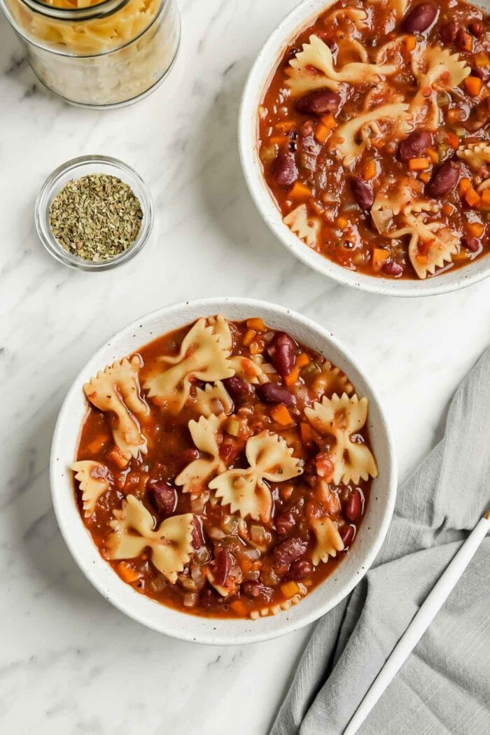 Overhead view of two bowls of minestrone soup with pasta and beans.