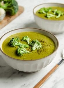 Two bowls of broccoli soup topped with a few pieces of broccoli.