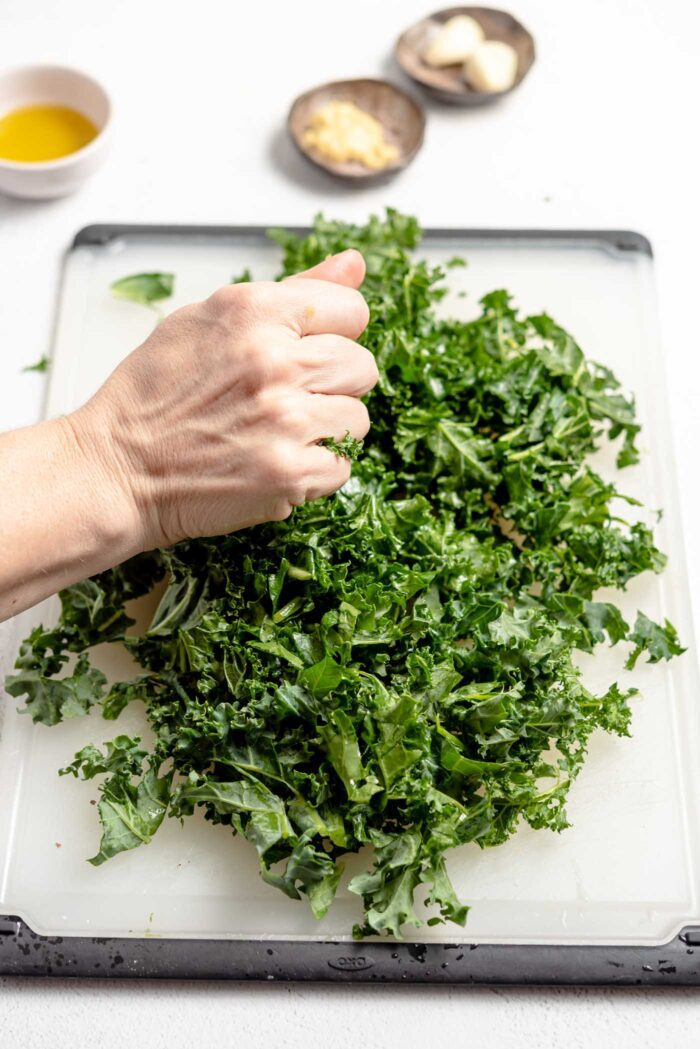 Hand squeezing a pile of chopped kale on a cutting board to soften it.
