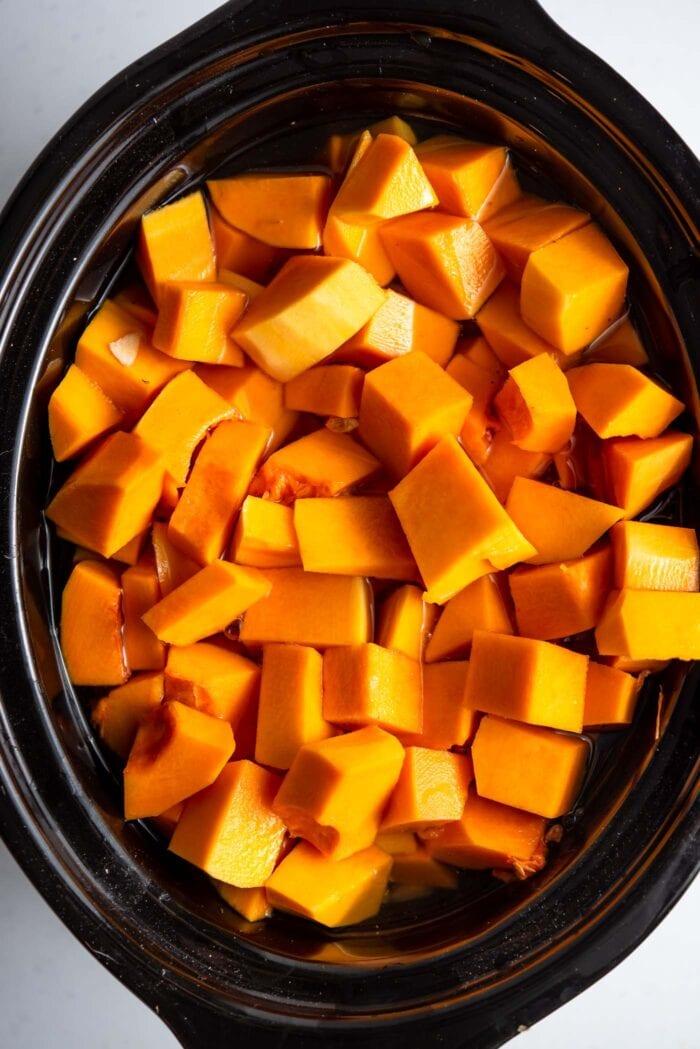 Cubed butternut squash in a crockpot.