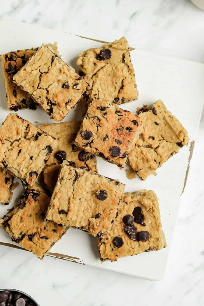 Numerous sliced chocolate chip blondies on a wooden cutting board.