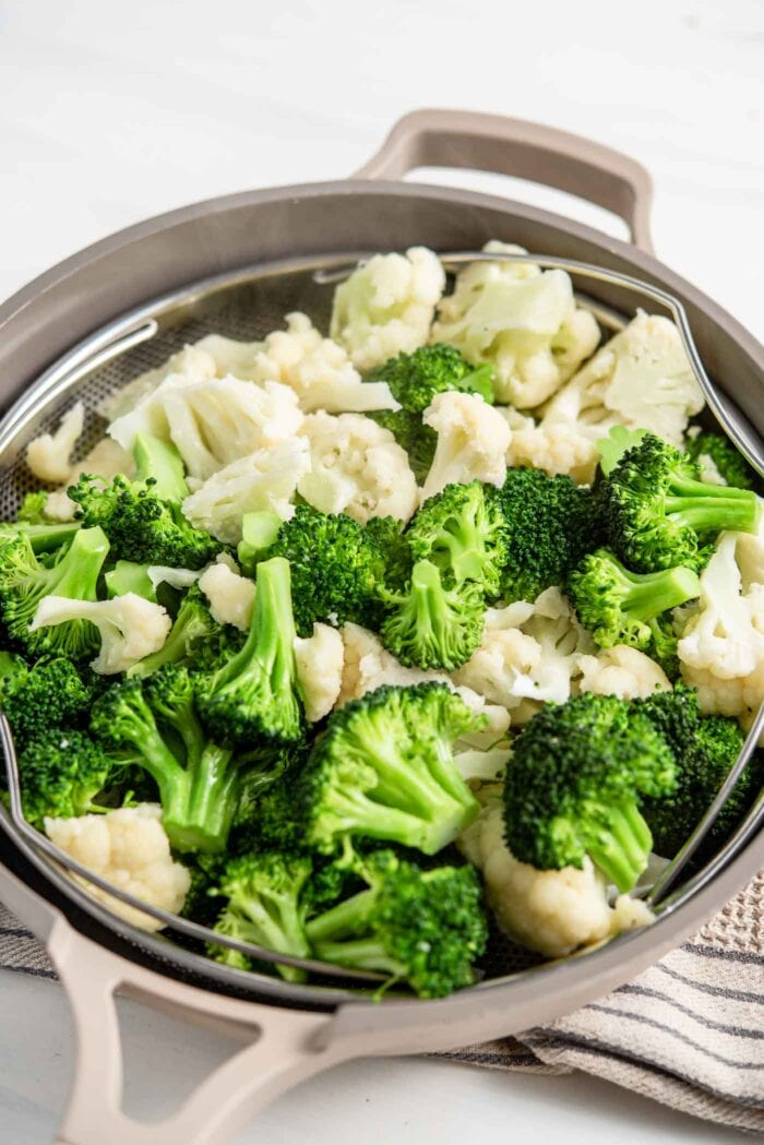 Steamed chopped broccoli and cauliflower in a steamer basket.