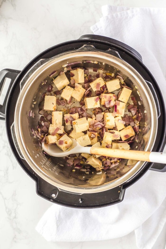 Tofu, onion and garlic cooking in an Instant Pot.