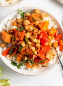 Overhead view of a bowl of sweet potato and chickpea curry topped with peanuts and over rice.