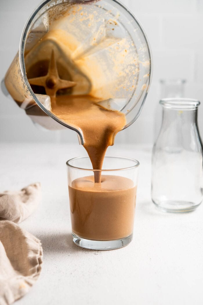 Blender pouring a creamy chocolate smoothie into a glass.