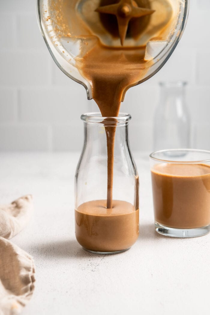 Blending pouring chocolate smoothie into a glass jar.
