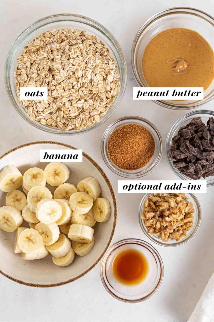Bowls of oats, banana, peanut butter, chocolate chips, vanilla, coconut sugar and walnuts.