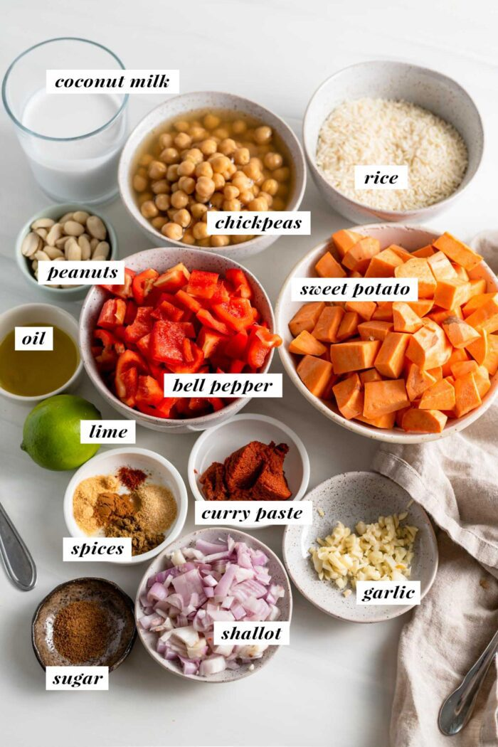 Visual of all ingredients needed for making a sweet potato chickpea curry. Each ingredient is labelled with text.