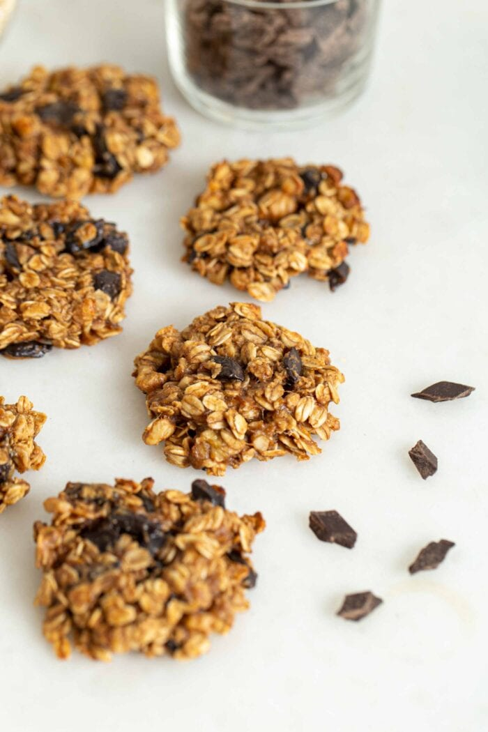 Oatmeal chocolate chip cookies sitting on a white surface with a few chocolate chips scattered around them.