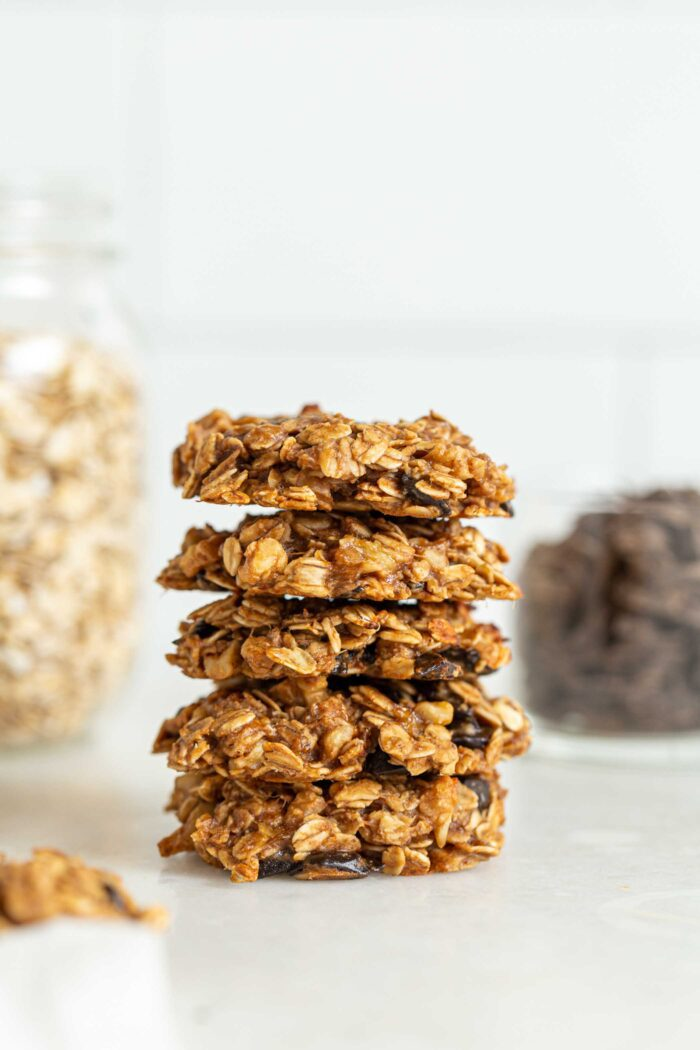 Stack of 5 oatmeal chocolate chips cookies with jars of oats and chocolate chips in the background.