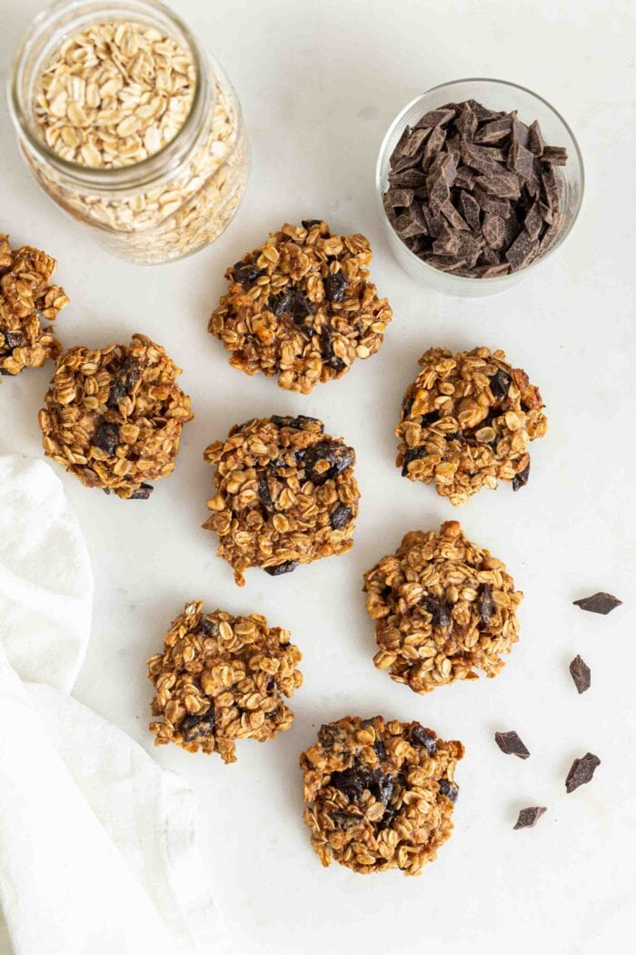 Oatmeal chocolate chip cookies on a white surface beside a jar of chocolate chips and jar of oats.