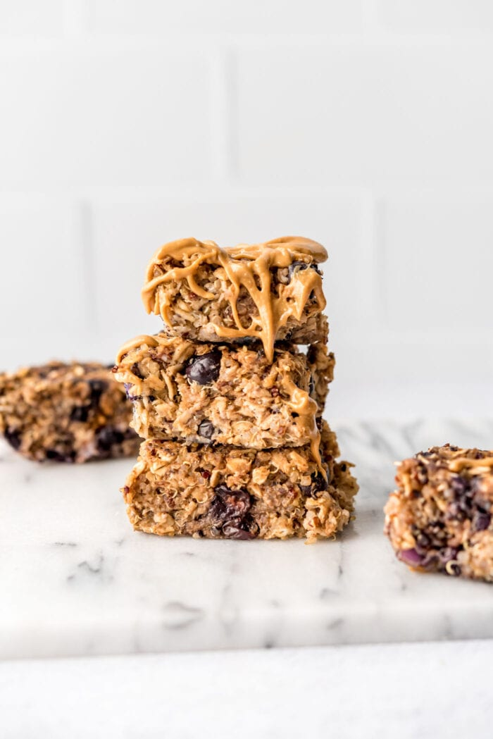 Stack of 3 baked blueberry quinoa oatmeal bars drizzled with peanut butter.