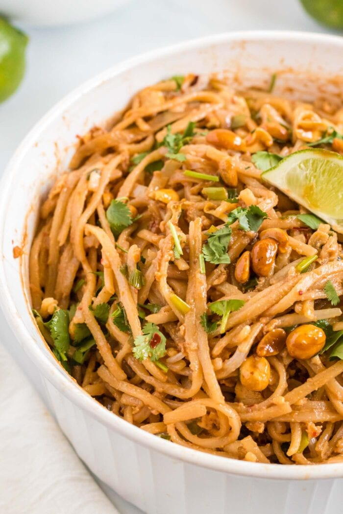 Close up of vegan tofu pad thai in a bowl topped with lime, peanuts and cilantro.