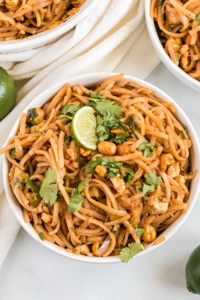 Vegetarian pad thai with tofu in a bowl topped with cilantro and a slice of lime.