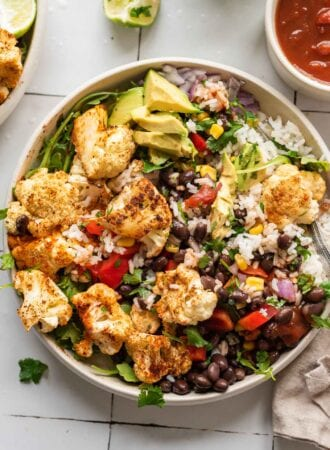 Overhead view of a burrito bowl with rice, roasted cauliflower, avocado and black beans.