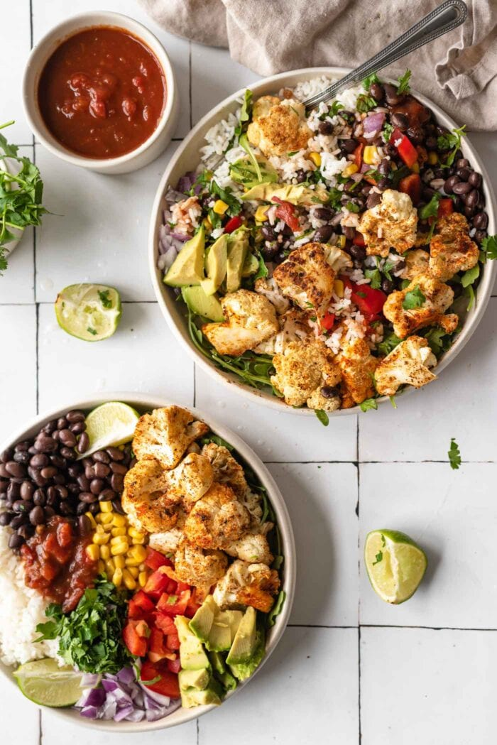 Overhead view of two burrito bowls with cauliflower, cilantro, avocado and lime.