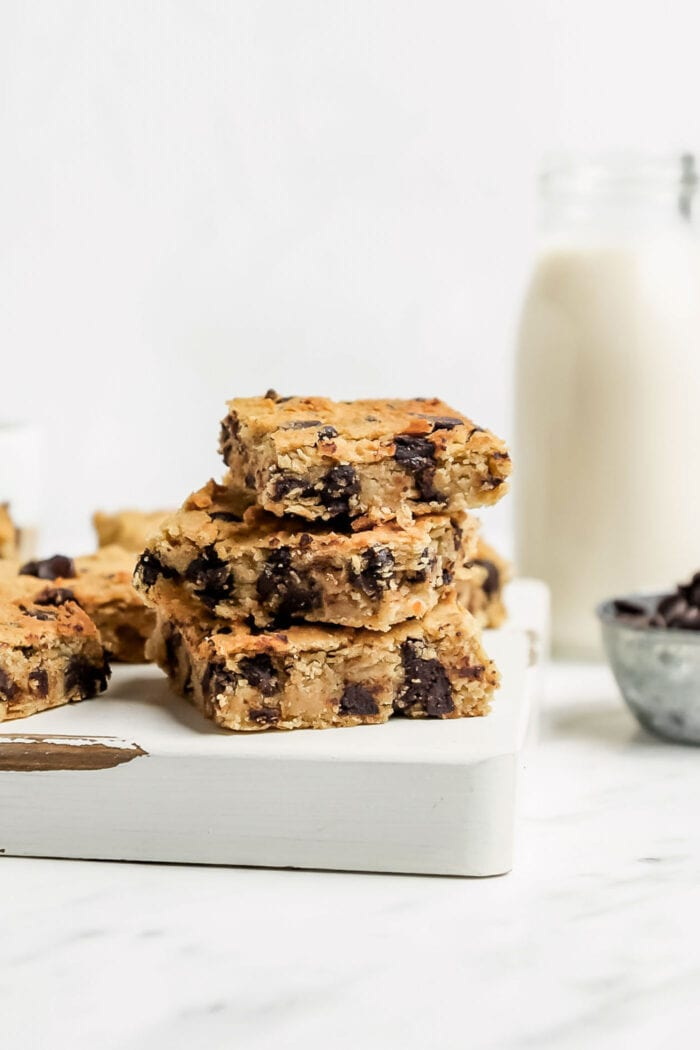 Stack of 3 chocolate chip blondies on a cutting board.