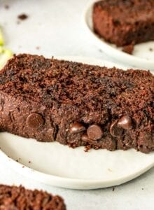 Thick slice of chocolate chip zucchini bread on a plate.