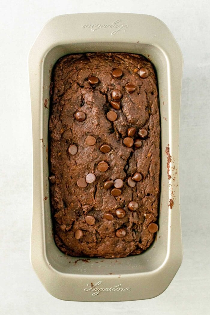 Baked chocolate loaf topped with chocolate chips in a loaf pan.