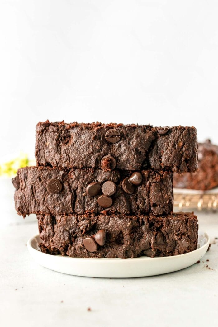 Three thick slices of chocolate chip zucchini bread on a plate.