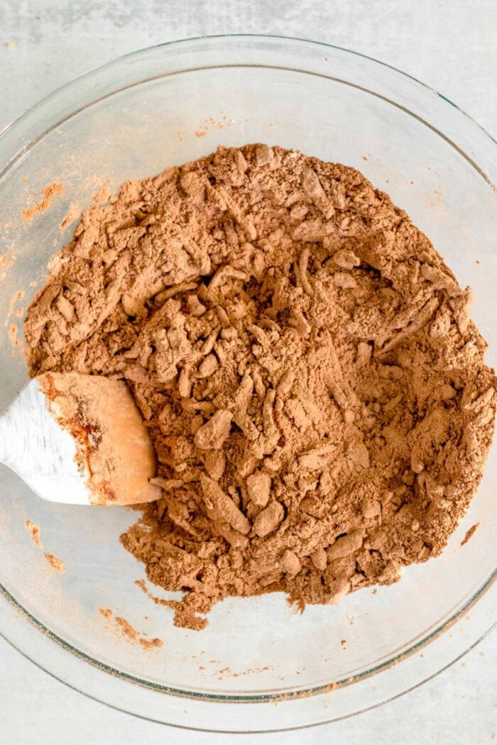 Spatula mixing grated zucchini into flour and cocoa powder in a glass mixing bowl.