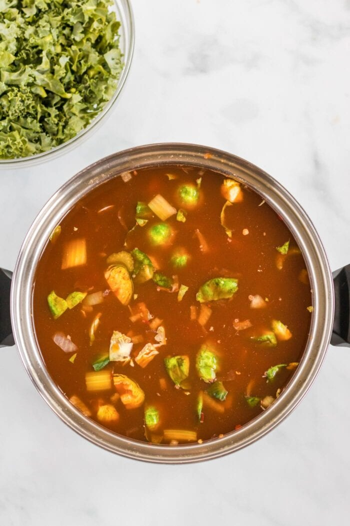 Vegetables cooking in a tomato broth in a large soup pot.