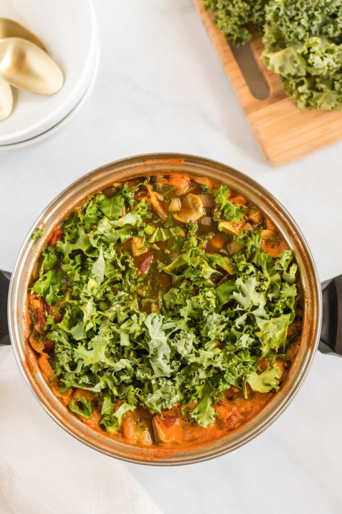 Chopped kale added to a large pot of soup.