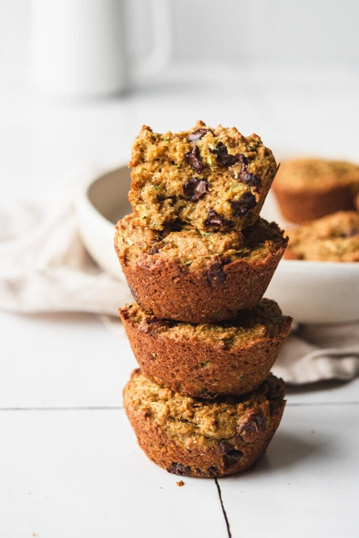 Stack of four chocolate chip zucchini muffins. Muffin on top is cut in half to show inside texture.